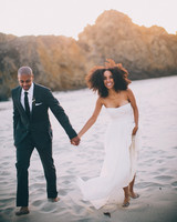 beach wedding dresses bride and groom holding hands walking on the beach