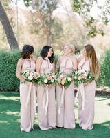 women standing on lawn wearing high neckline with cutout bridesmaids jumpsuits