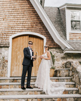 bride and groom with champagne in front of house converted from a stone barn
