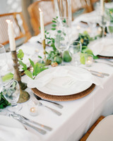 wedding place settings greenery and candle stick centerpieces