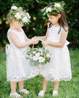 two flower girls holding a white wicker basket