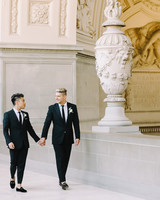 grooms walk outside city hall holding hands