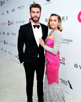 miley cyrus and liam hemsworth posing on red carpet