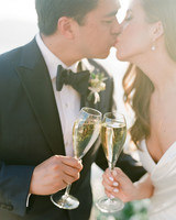 bride and groom kissing and toasting champagne glasses