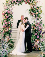 stephanie joe wedding floral ceremony arch and couple kissing