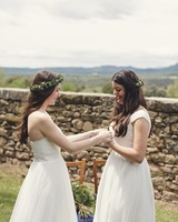 brides holding hands wearing flower crowns