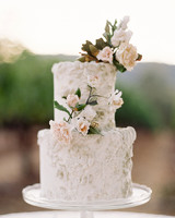two tiered textured white frosting wedding cake with floral accents