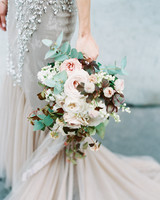 bride holding bouquet of roses and white flowers