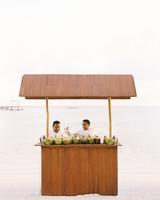 sara danny mexico wedding couple coconut stand on beach