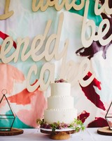 "colorful dessert table backdrop ""I Told You There'd Be Cake"" with floral vanilla wedding cake"