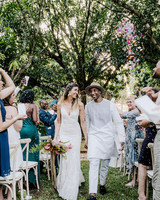 bride and groom holding hands smiling during recessional