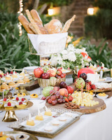 table with fruit, baguettes, and desserts