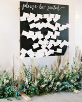white table escort cards with handwritten notes on black board