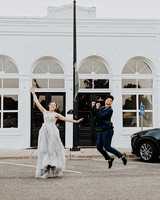 brides mid-jump in front of venue