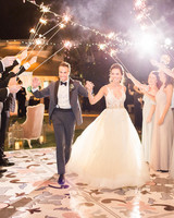 bride and groom celebrate first dance with guests under sparkler archway