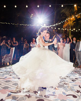 guests gather around bride and groom for first dance