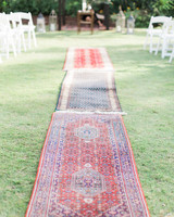 red and blue patterned boho rugs line the wedding aisle