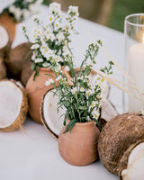 broken coconuts, terra cotta pots, and white floral table decor