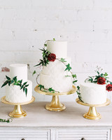three white frosted wedding cakes with greenery and floral accents