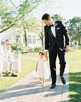 flower girl walks down aisle with her dad during processional