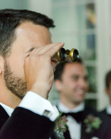 groom viewing bride through vintage binoculars