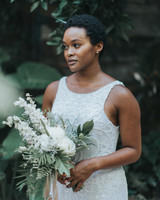 bride standing amongst greenery holding tropical bouquet