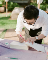 hawaiian wedding man signs guest book with pink pen