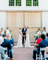 paige and kristine wedding ceremony in front of barn doors