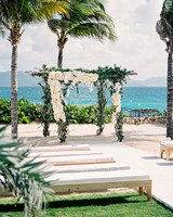 ocean front outdoor wedding reception area with benches and palm trees