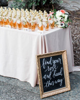 alcohol escort cards rose half bottles on table