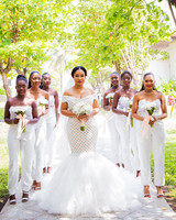 women wearing white strapless bridesmaids jumpsuits holding white floral bouqets