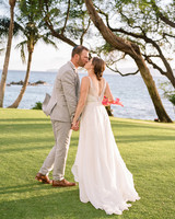 bride and groom hold hands while kissing on green lawn