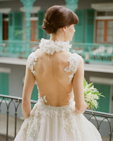A Bride Wearing a Wedding Dress with a Dramatic Back Looking Over a Balcony