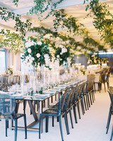 melissa justen wedding reception tables with tall floral centerpieces and hanging greenery