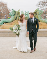 bride and groom smile at each other in front of fountain