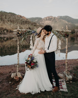 elopement outfit inspiration couple kissing beneath arch created from sticks and flowers