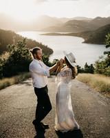 bride wearing white hat kissing groom