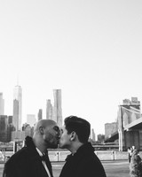 grooms kissing city skyline