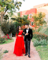 bride and groom in reception outfits standing in garden