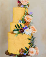 floral and fruit covered three tiered yellow frosted cake