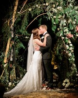 wedding bride groom kiss below greenery white flower arch