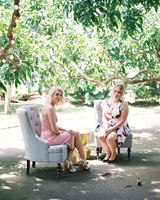 guests pose on vintage chairs outside