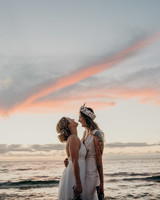 sunset wedding photos brides embracing and laughing on beach