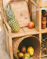 woven rattan wedding decor shelves with titki glasses and fruit
