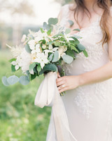 bride holding a dogwood and eucalyptus bouquet