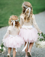 two flower girls in cardigans and tutus