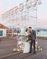sunset wedding photos bride and groom kissing on rooftop