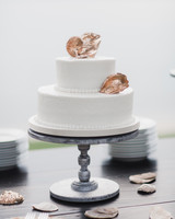 Two-Tiered White Wedding Cake Topped with Gold Shells