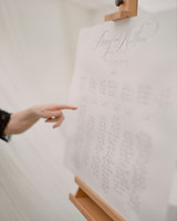 peony matthew england wedding hand pointing to seating chart