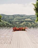 wedding ground floral arch red arrangement ghost chairs